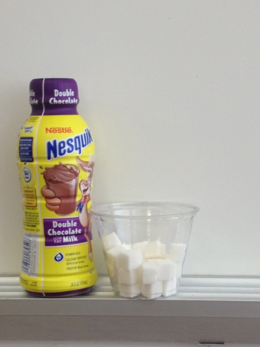 Bottle of Nesquik chocolate milk next to a glass of sugar cubes.